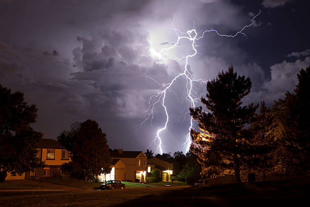 Lightning bolt and thunderhead storms over Denver neighborhood homes stock photo