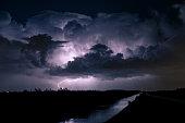 Majestic Cumulonimbus storm cloud at night is illuminated by lightning.