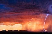 A lightning bolt strikes next to the setting sun as a thunderstorm moves through the desert near Salome, Arizona.