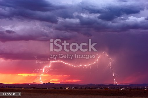 1039163636 istock photo Lightning bolt strike from a storm at sunset 1172798117