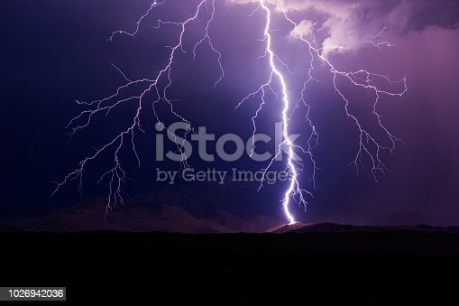 istock Lightning bolt strikes a mountain during a storm. 1026942036