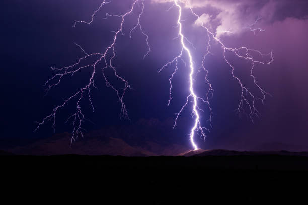 Lightning bolt strikes a mountain during a storm. stock photo
