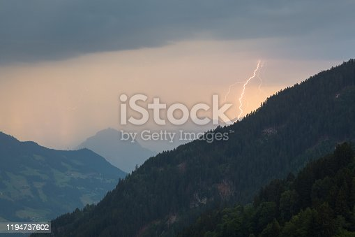 1039163636 istock photo Lightning bolt strikes down between the mountains of the Alps, Europe 1194737602