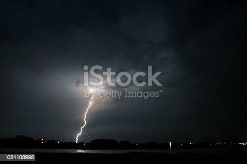 656192770 istock photo A lightning bolt strikes down from a severe thunderstorm near the river Waal in The Netherlands. 1084108998