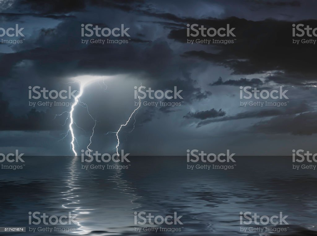 lightning bolts reflection over the sea stock photo