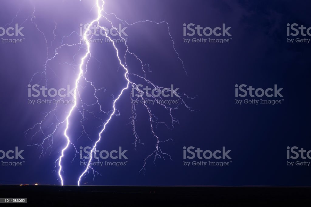Lightning bolt strike from a storm at night with a dark sky...