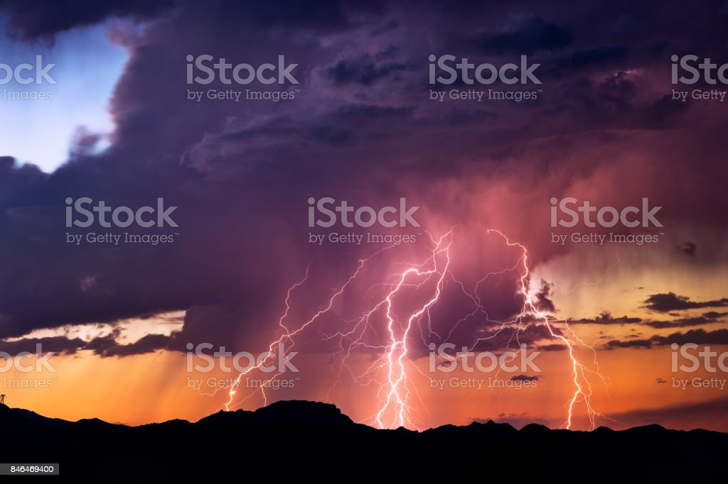 Lightning bolts strike from a sunset storm stock photo