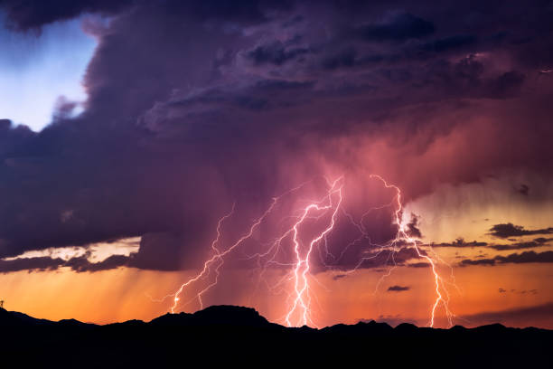 lightning bolts strike from a sunset storm - cielo minaccioso foto e immagini stock