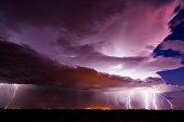 Dramatic lightning bolts strike from a monsoon thunderstorm at night near Wintersburg, Arizona.