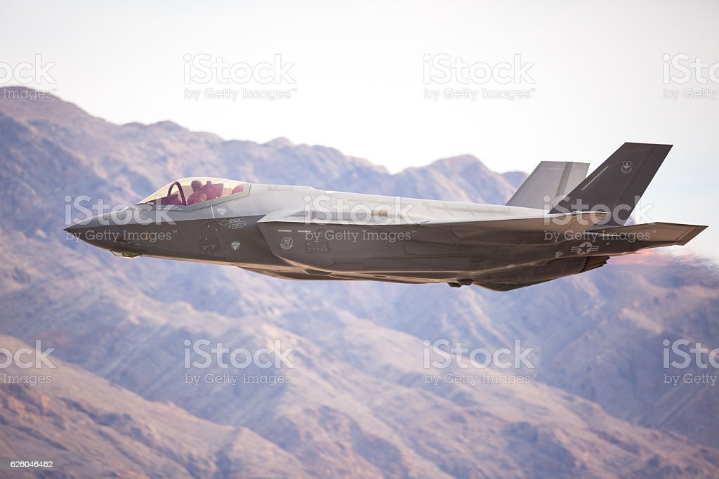 F-35 Lightning II against the Nevada hills, with afterburner on stock photo