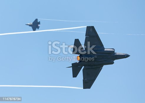 1145066973 istock photo F35 Lightning II   in a  high G maneuver, with condensation trails forming  at the wings tip and afterburners on, during a dogfight with another F-35 1147676734