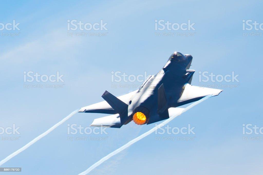 F-35 Lightning II en una maniobra de alta aceleración, con dispositivo de poscombustión en y senderos de condensación en el borde del ala - foto de stock