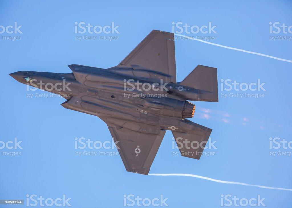F-35 Lightning II en una apretada gira, con dispositivo de poscombustión en y senderos de condensación en el borde del ala - foto de stock