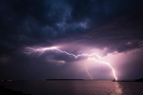 lightning in the dark night sky over a lake during summer - lightning zdjęcia i obrazy z banku zdjęć