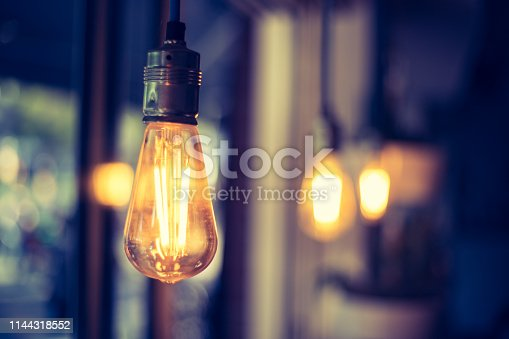 Close up picture of a hanging orange lightbulb in a restaurant or café
