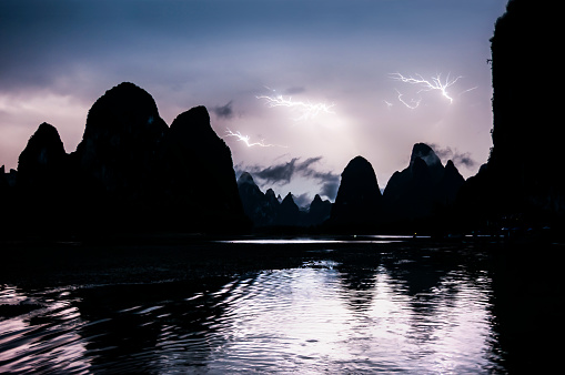 Yangshuo: tourists on night light show with natural scene in Yangshuo city in rain. Town is resort destination for domestic and foreign tourists because of scenic karst peaks