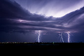 Lightning storm with several bolts striking over a city in Texas.