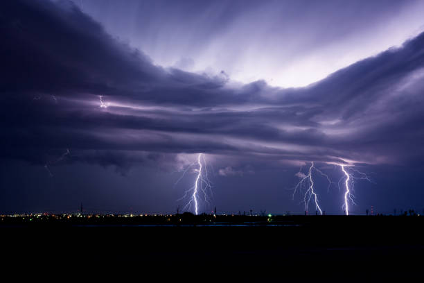 lightning over a city - extreme weather stock pictures, royalty-free photos & images