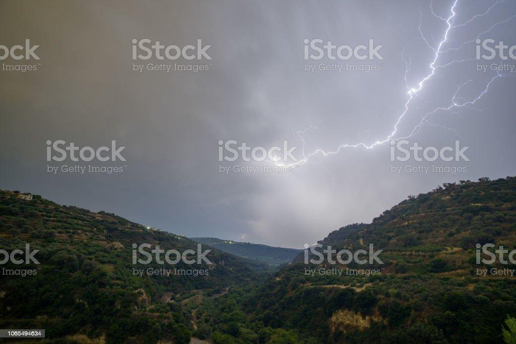 Lightning over hills stock photo