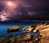Lightning over the coast of the Black sea. Rocky coast of the Eastern Crimea. Near Koktebel. The power and energy