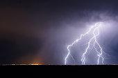 Lightning bolts strike from a thunderstorm.