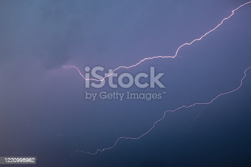 503731700 istock photo Lightning shoots across a clear evening sky 1220998962
