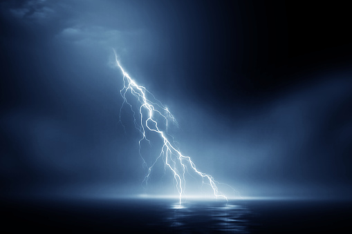 Impressive natural image of erratic lightning bolts hitting the surface of the water at night.