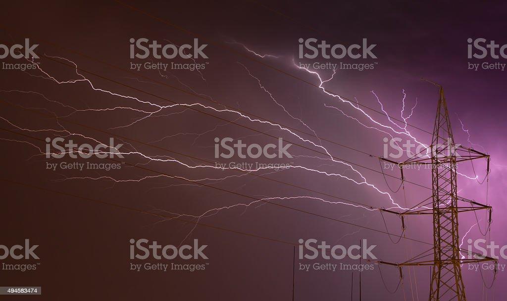 Lightning Storm behind Electricity Pylon stock photo