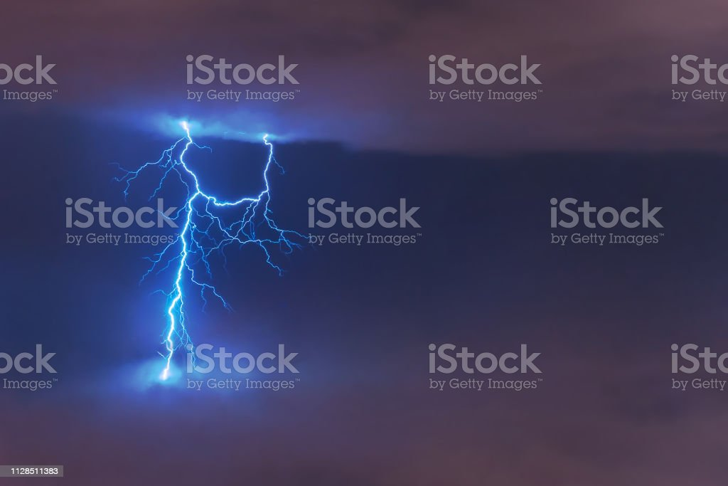 Lightning strike flash, electric discharge between clouds at night. stock photo