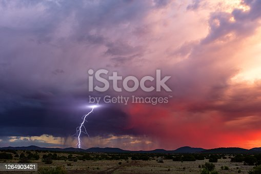 1039163636 istock photo Lightning strike from a storm at sunset 1264903421
