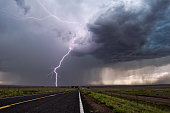 Lightning bolt strike from a thunderstorm with dark clouds and rain.