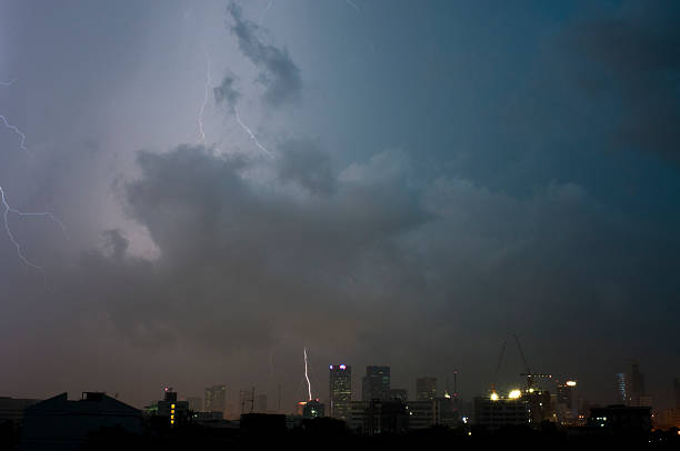 lightning strike in the city - lightning stock photos and pictures