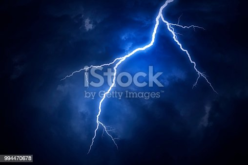 istock A lightning strike on a cloudy dramatic stormy sky 994470678
