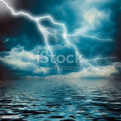 istock Lightning strike on the dark cloudy sky over the sea 653064722