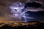 A lightning strike illuminates the clouds over a city on the tailing edge of a storm.