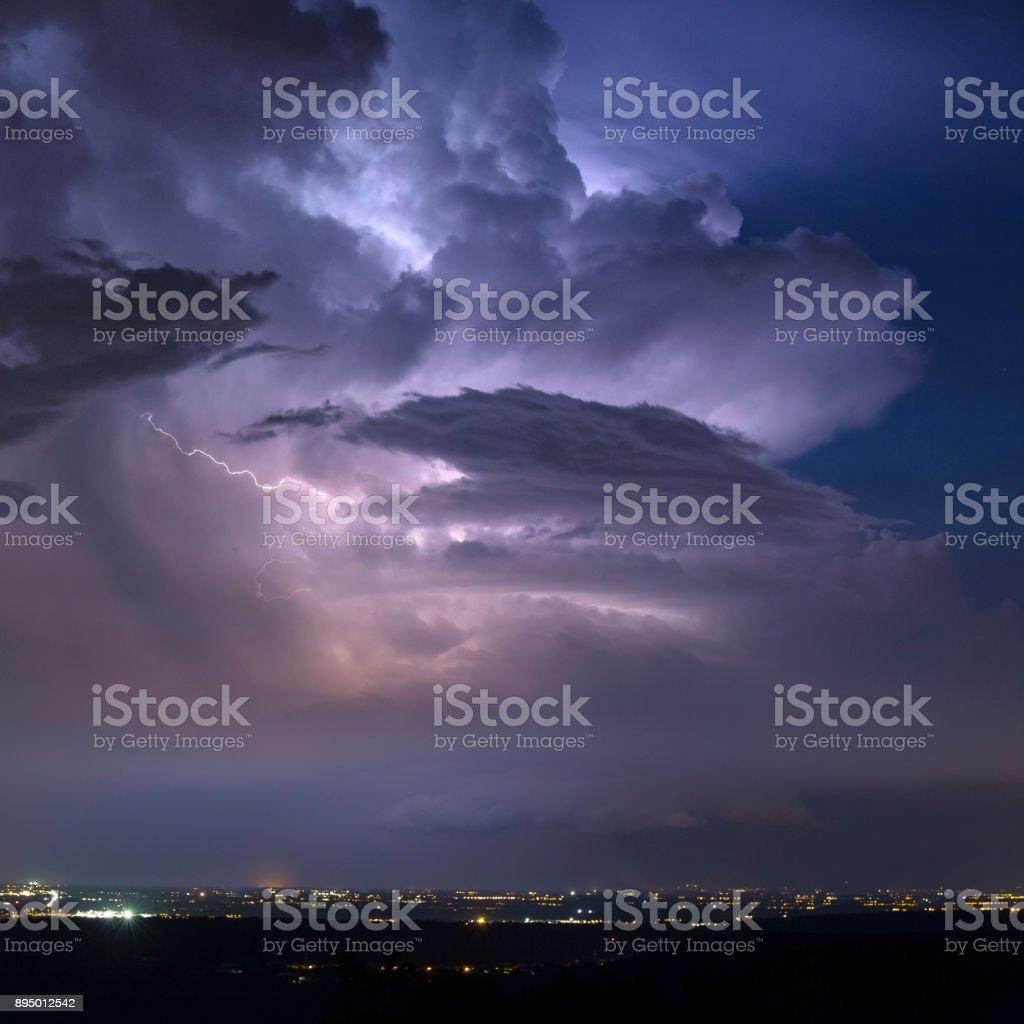 Lightning strike through a storm cloud stock photo