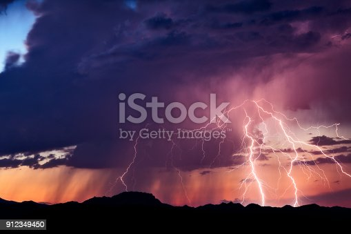 Lightning bolts strike from a monsoon thunderstorm at sunset, in the desert near Congress, Arizona.