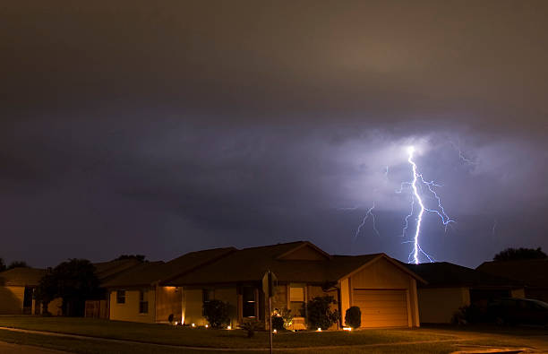 Lightning strikes in the night near family houses stock photo