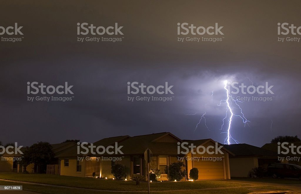 Lightning strikes in the night near family houses stock photo