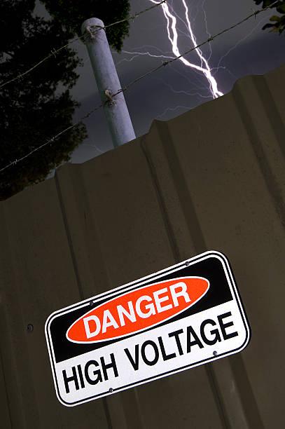 Lightning strikes near High Voltage sign stock photo