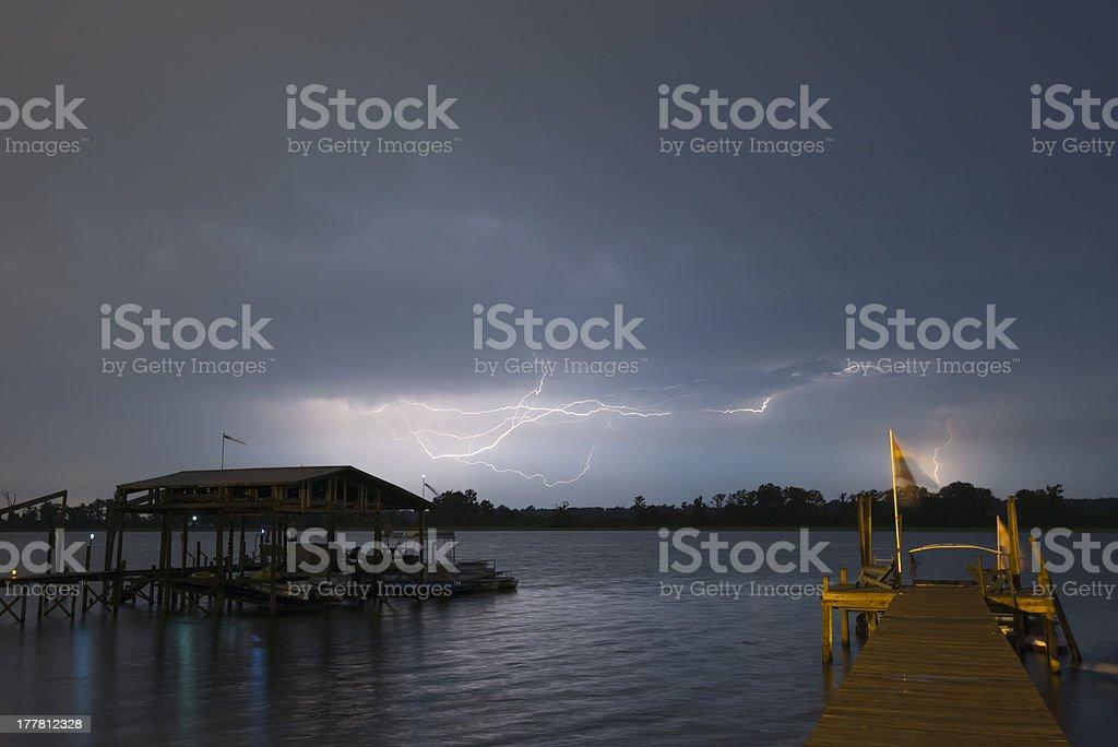 Lightning striking over a lake stock photo