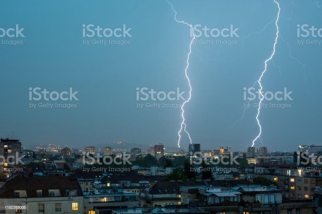 Lightning Thunderbolt Flash Strike Over City in the Night. Weather...
