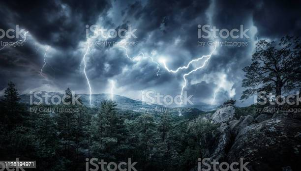 Photo of Lightning thunderstorm flash in the mountains. Concept on topic weather, cataclysms (hurricane, Typhoon, tornado, storm)