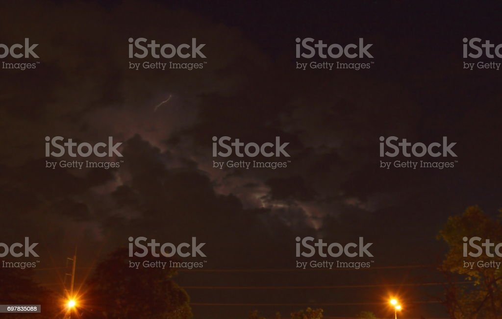 lightning with rain cloud in night and lamp post on street