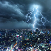 Bright lightnings illuminates a cityscape with skyscrapers, while dark cumulonimbus and clouds hover through the sullen sky. Natural dangers, buildings problems and majestic beauty. Real cloudscape and metropolis panorama with digital lightning. Copy space on image side.