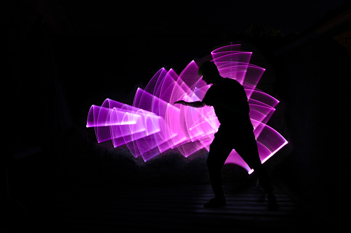 Silhouette of a man in profile with outstretched arm. Abstract light saber shape in background.