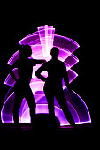 Silhouette of two women in front. Girl leaning on the shoulder of her friend. Abstract curved shape, pink color with a light saber in the background.