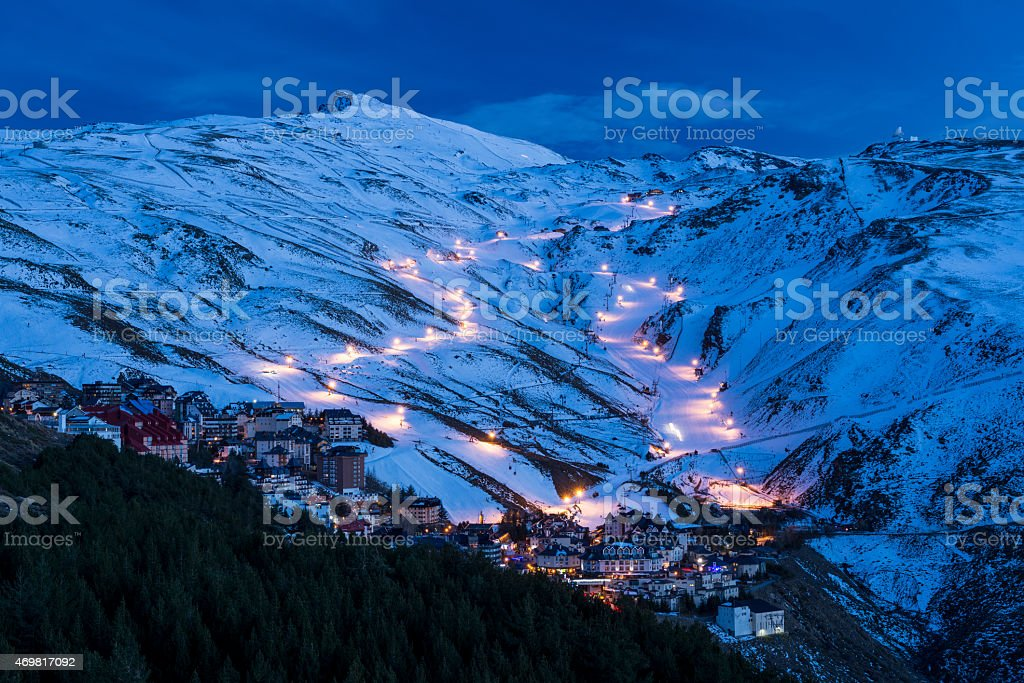 Lights at night in snowy hills in Sierra Nevada stock photo