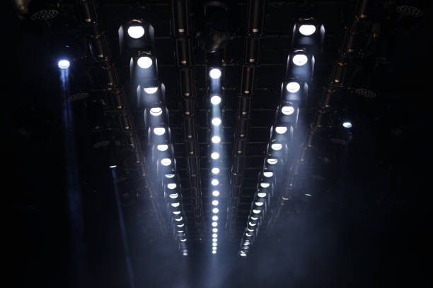 Lights beams Spotlight ray moving lighting on rack construction ceiling Many Par Led Lights beams Spotlight ray moving lighting on rack construction ceiling, for Fashion Show Event performance in dark room hall for fashion show style decorated floor ramp stock pictures, royalty-free photos & images