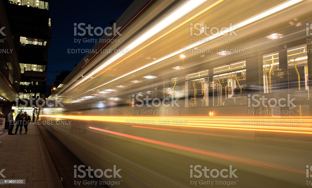 Lights of a moving tram at night. stock photo